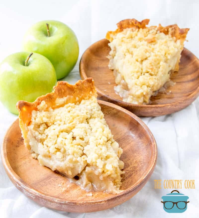 Southern Apple Pie with Streusel Topping recipe. Two slices shown on two small round wooden plates with two green apples in the background.