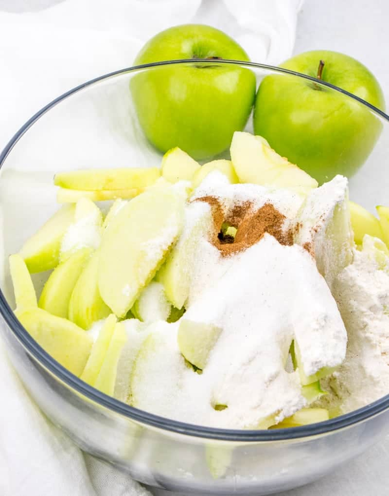 sliced green apples, flour, cinnamon, sugar tossed together in a bowl