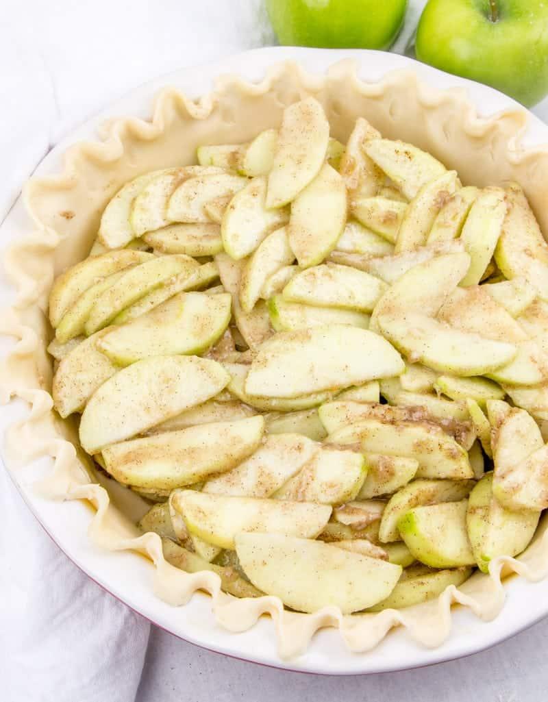 apple pie filling layered into pie crust.