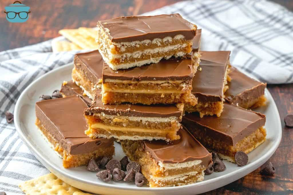 Homemade Kit Kat Bars, sliced and layered on top of a plate with crackers and chocolate chips scattered around