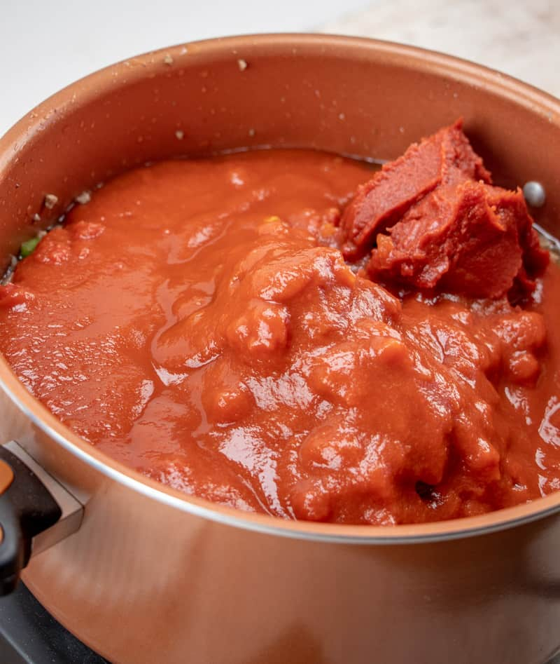 tomato sauce, diced tomatoes added into cooked ground beef mixture in large pot