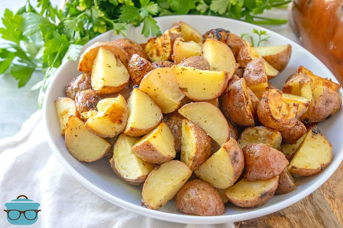 FINISHED, RANCH ROASTED POTATOES SERVED IN A WHITE BOWL WITH PARSLEY