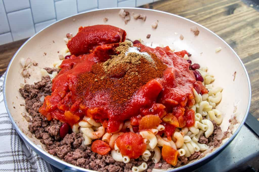cooked macaroni noodle, tomato sauce, garlic, chili powder and diced tomatoes added to cooked ground beef in the sauce pan