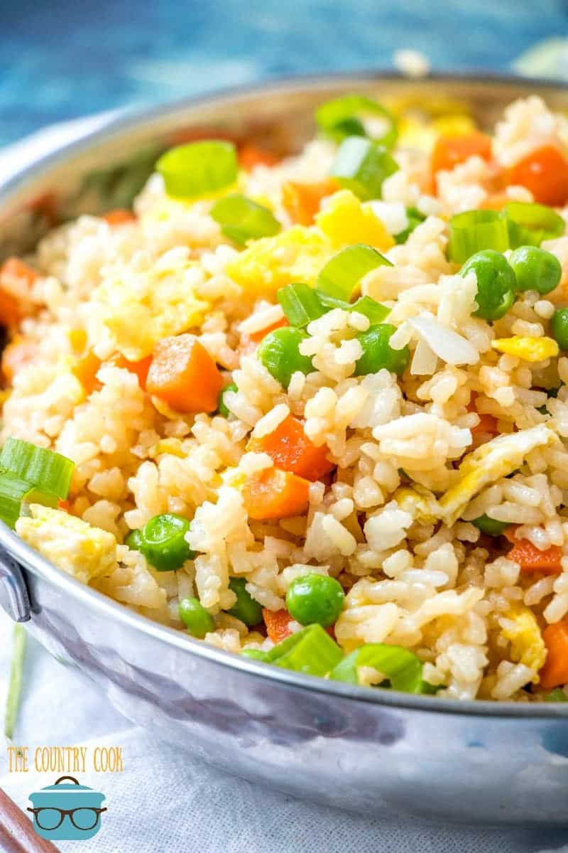 Easy Homemade Fried Rice shown in a silver skillet topped with sliced green onions.