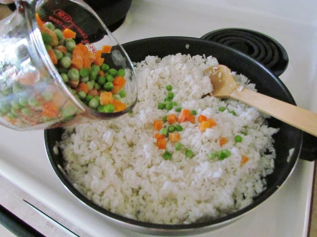 peas and carrots added to white rice