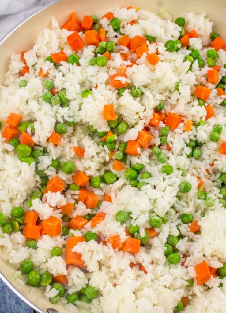 peas and carrots added to cooked rice in a large skillet