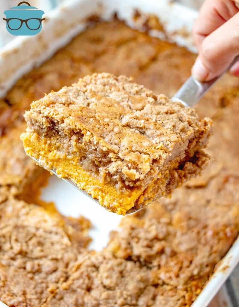 PUMPKIN DUMP CAKE in baking pan, slice served on a spatula.