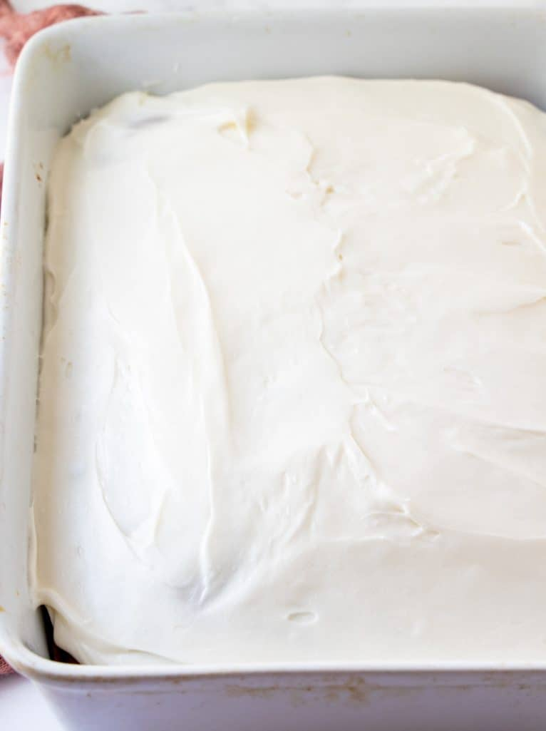 cream cheese frosting spread onto goole pumpkin spice cake in a white baking dish