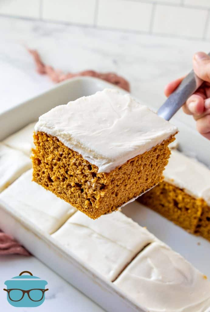 sliced pumpkin spice cake in a baking dish, one slice shown raised above the cake on a spatula