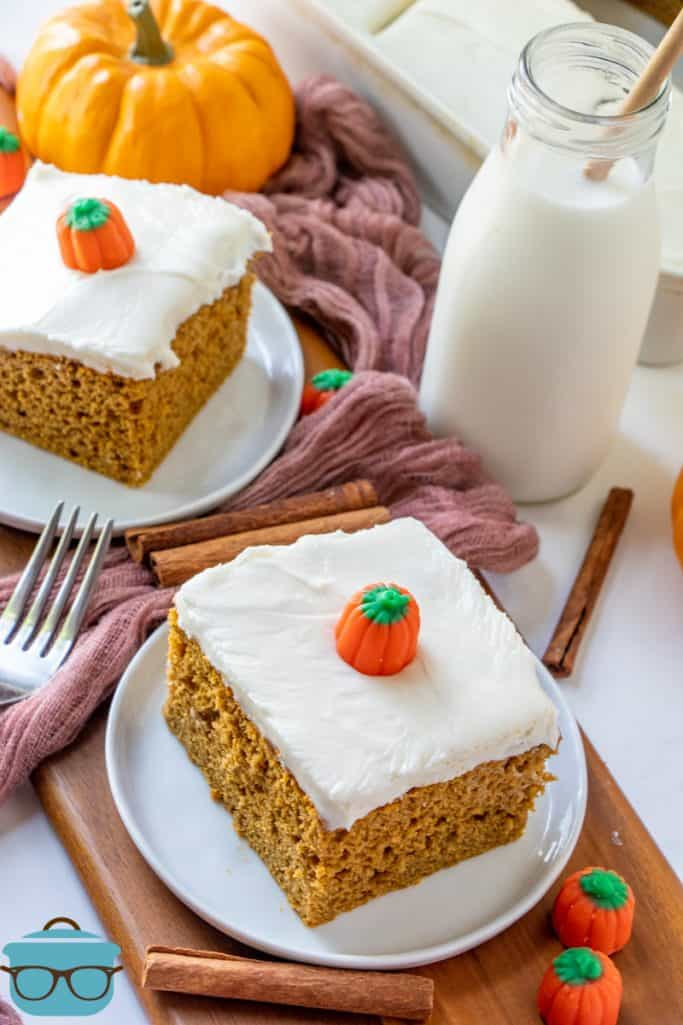 Two slices of pumpkin spice cake shown on small white plates with a bottle of milk in the background