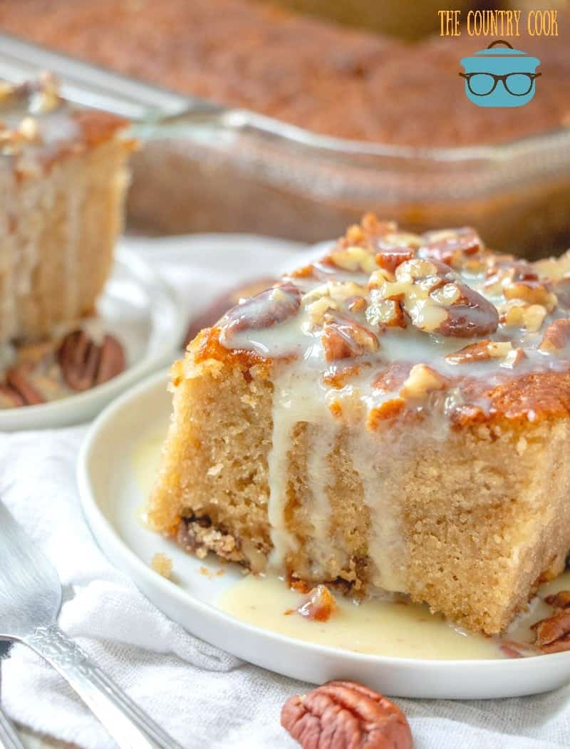 slice, pecan praline cake with butter sauce and topped with chopped pecans shown on a small round white plate.