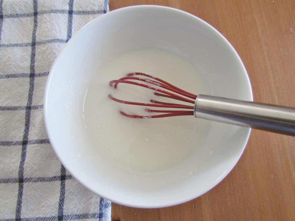 powdered sugar and milk whisked together in a bowl