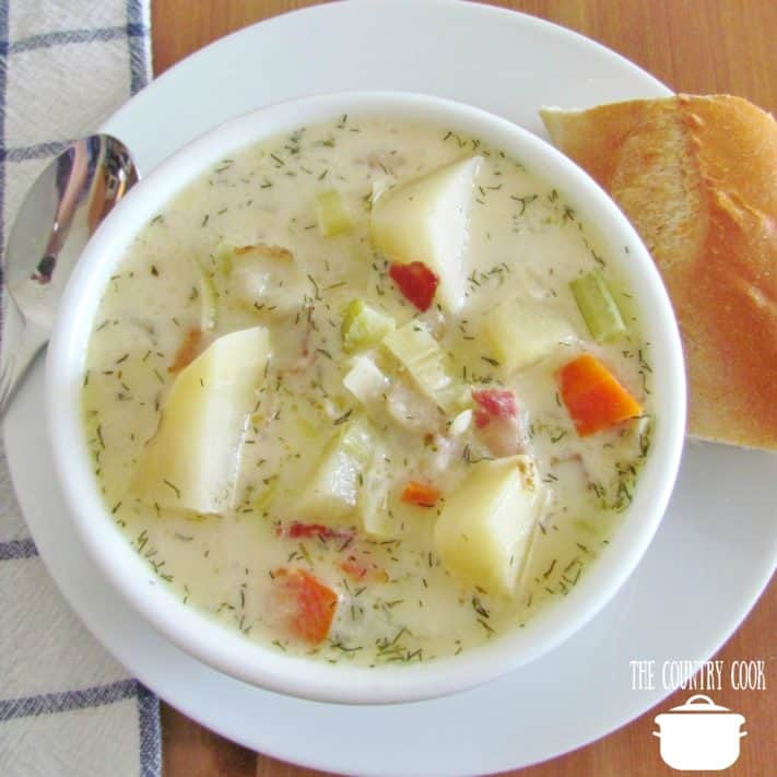 Leek and Potato soup with bacon served in a white bowl with a chunk of baguette bread