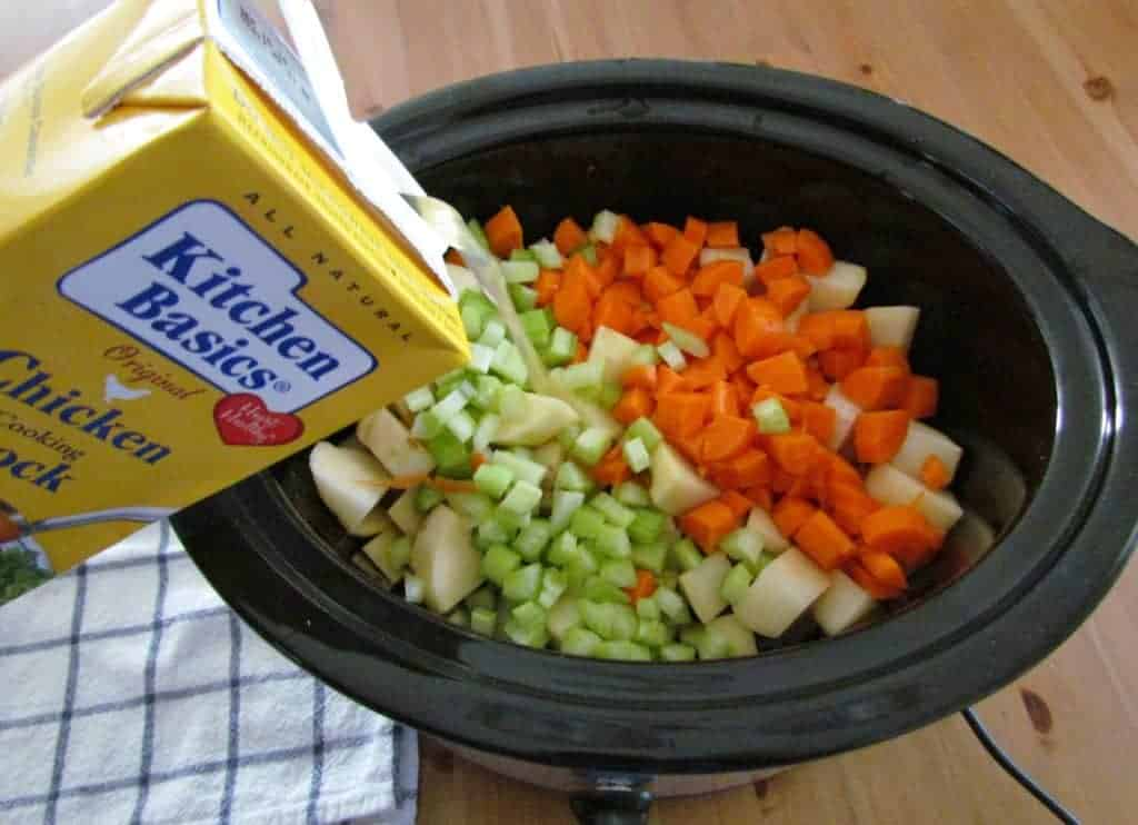 pouring Kitchen Basics chicken stock into slow cooker with diced vegetables