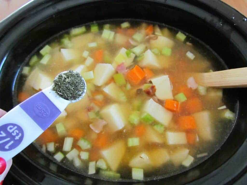 adding dill weed and garlic powder into crock pot with leeks and potatoes