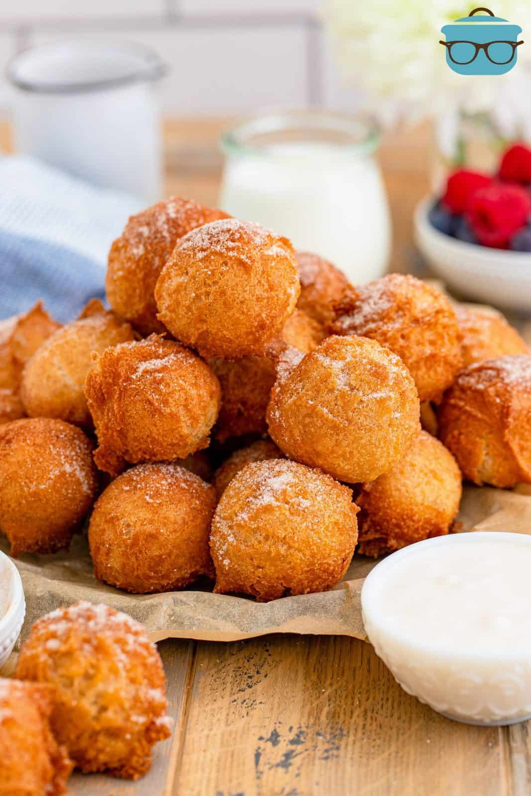 pancake puppies stacked on brown parchment paper with glasses of milk in the background.