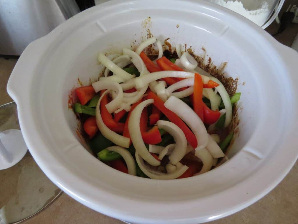 adding sliced peppers and onions to beef strips