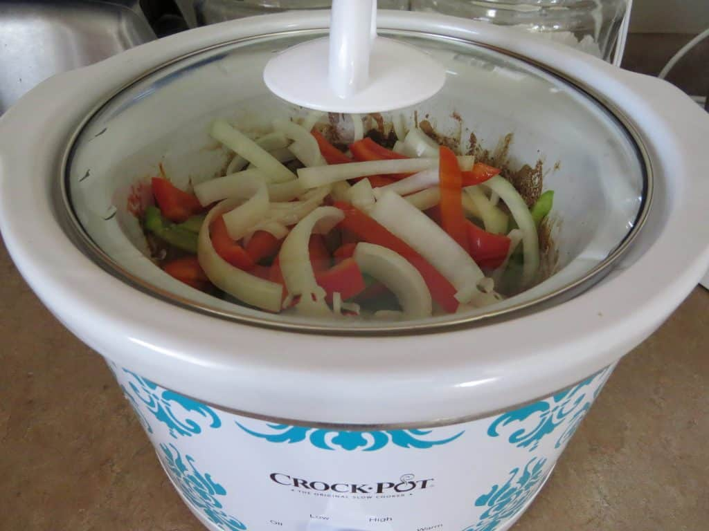 covered beef strips with peppers and onions