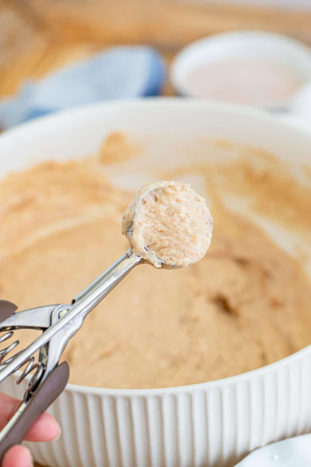 spring loaded scooper with pancake puppy batter being scooped from a bowl of batter.