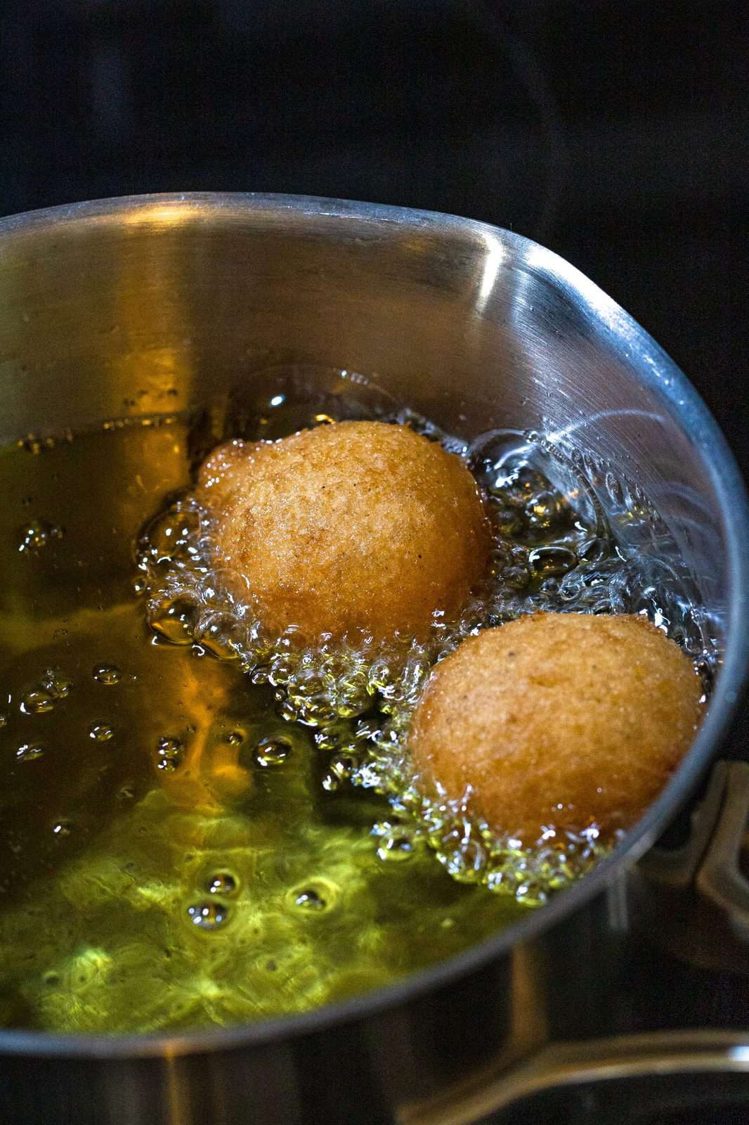 pancake puppies being shown frying in oil in a pot.