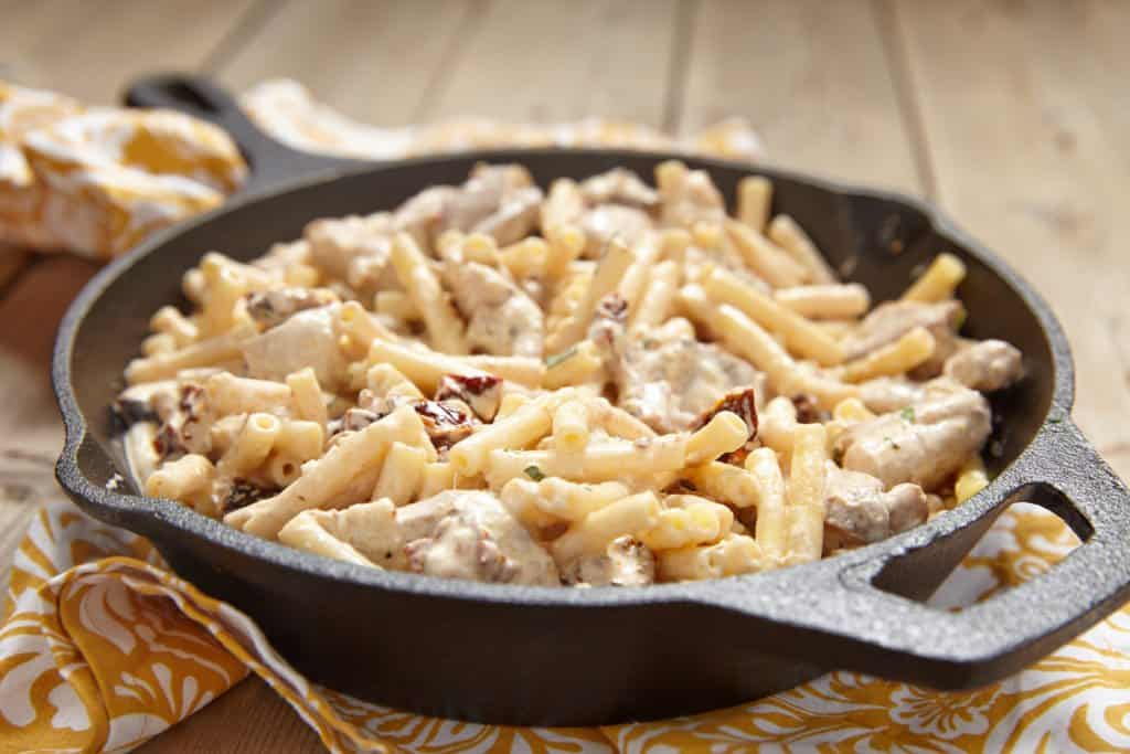 Crock Pot Creamy Italian Chicken and Pasta in a cast iron skillet