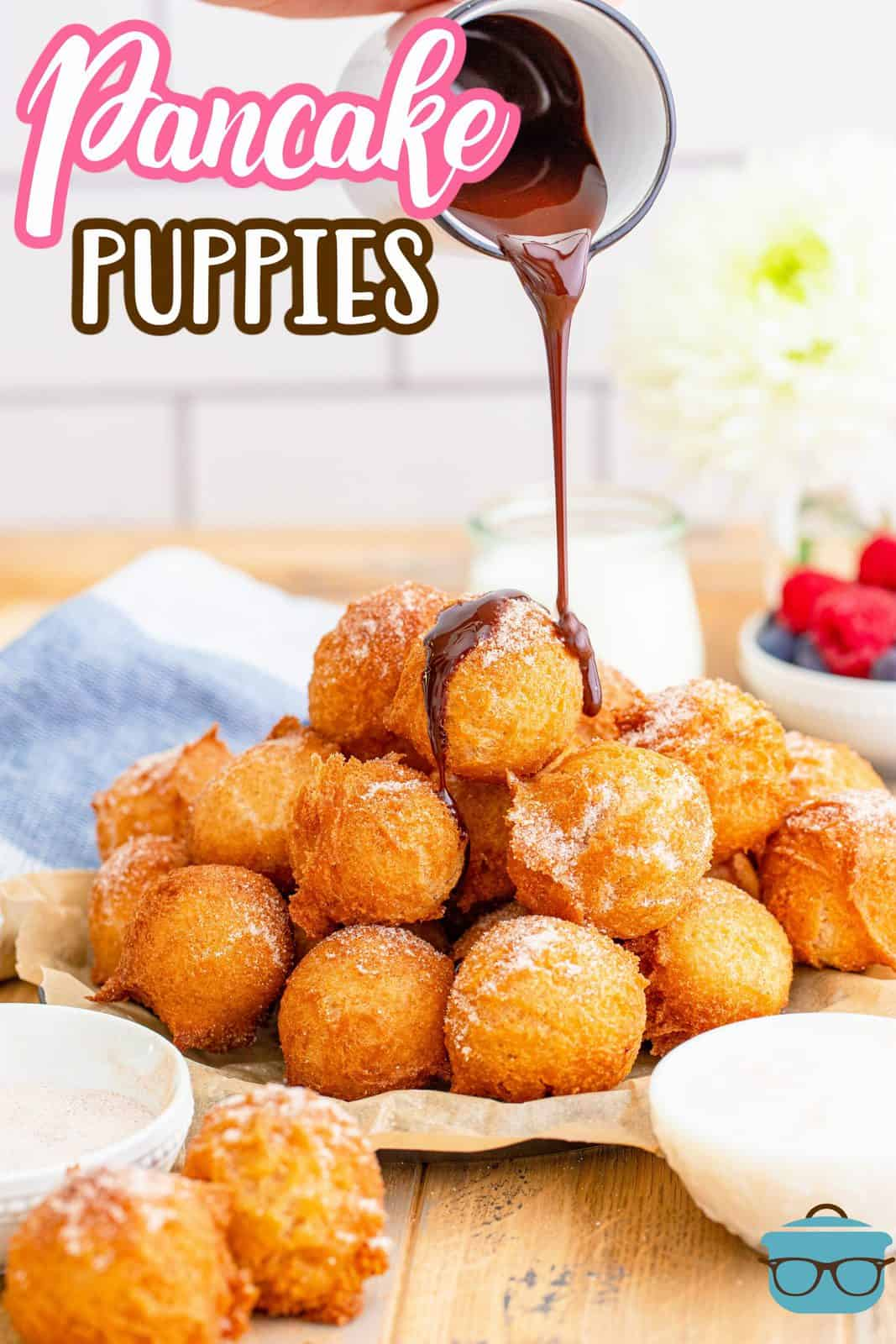 pancake puppies shown stacked on a plate with chocolate sauce being drizzled on top.