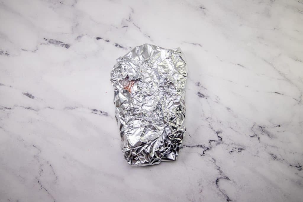 roast wrapped in aluminum foil on a marble surface
