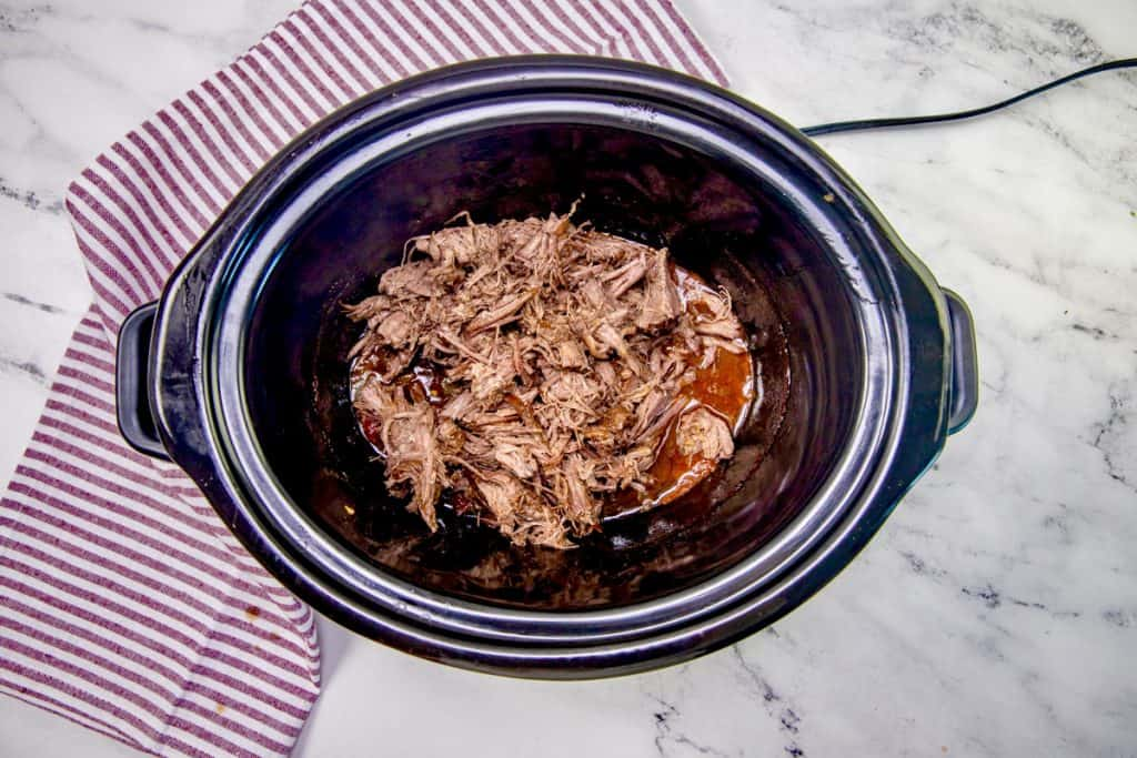 cooked and shredded chuck roast in a black oval slow cooker