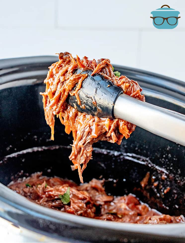 Mexican-Style Shredded beef shown being held in tongs over the slow cooker