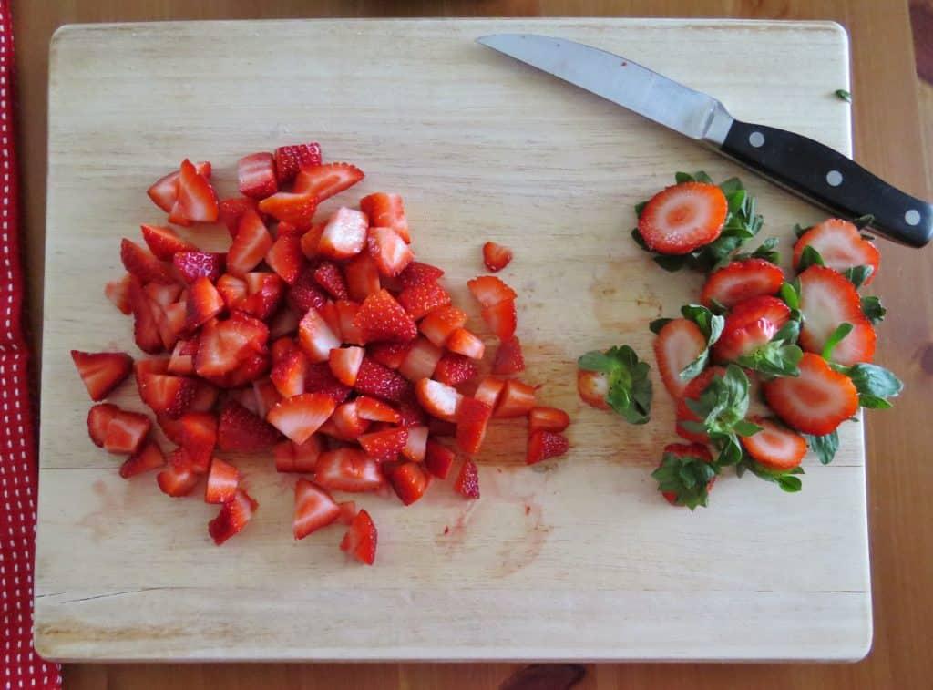 fraises fraîches en dés sur une grande planche à découper en bois