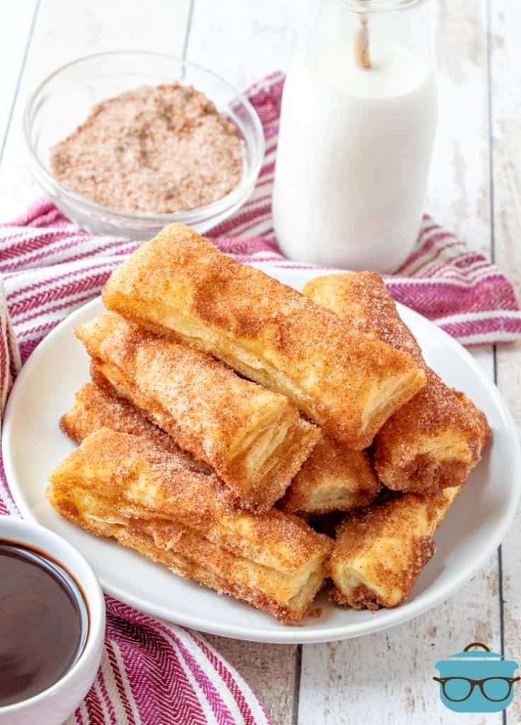 Puff Pastry Churros on a plate with a bottle of milk in the background