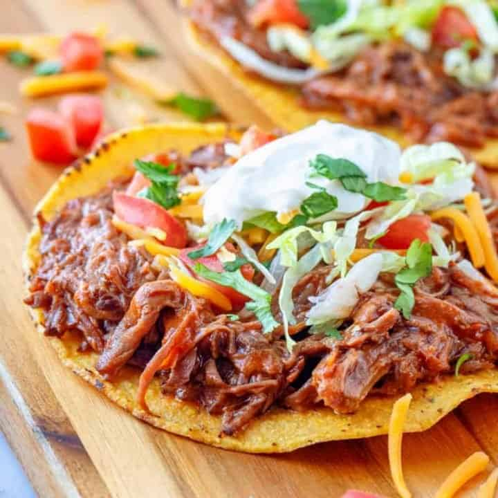 Crock Pot Mexican Shredded Beef shown served on a tostada