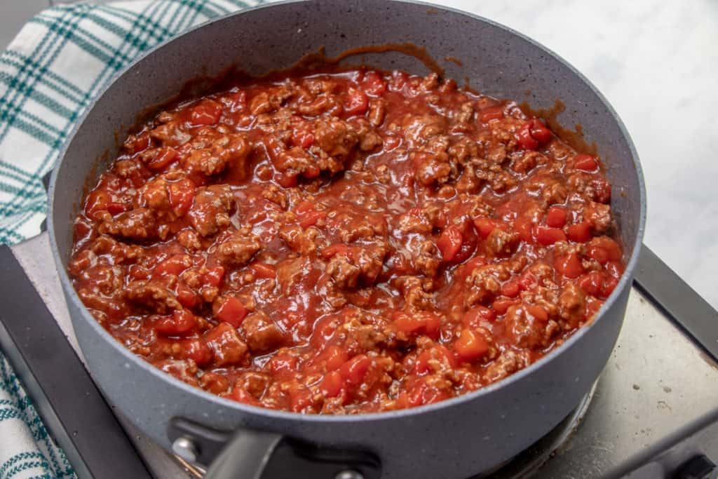diced tomatoes, barbecue sauce, Worcestershire sauce and sugar added to cooked ground beef added to the skillet, stirred together