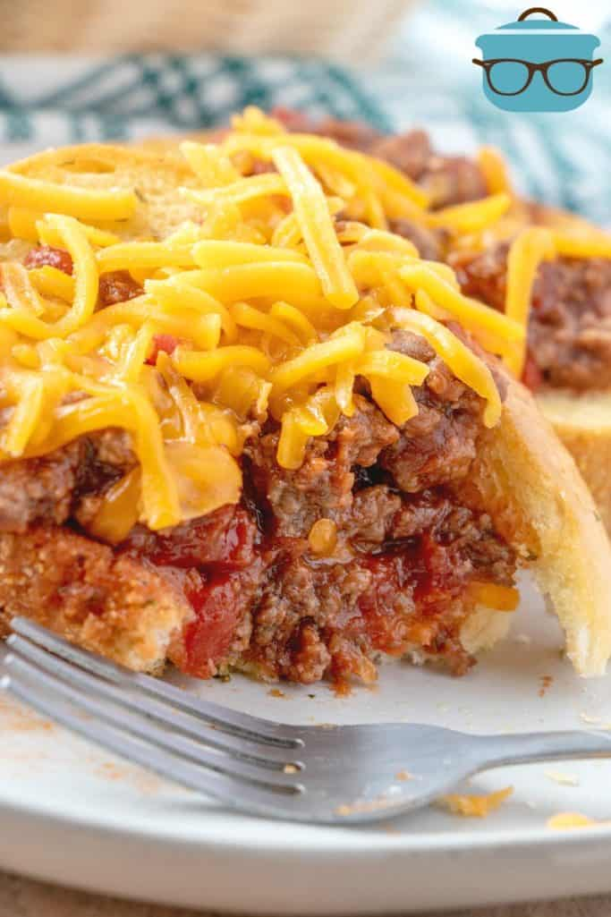 BBQ Sloppy Joe filling on top of garlic Texas toast with shredded cheddar cheese on top