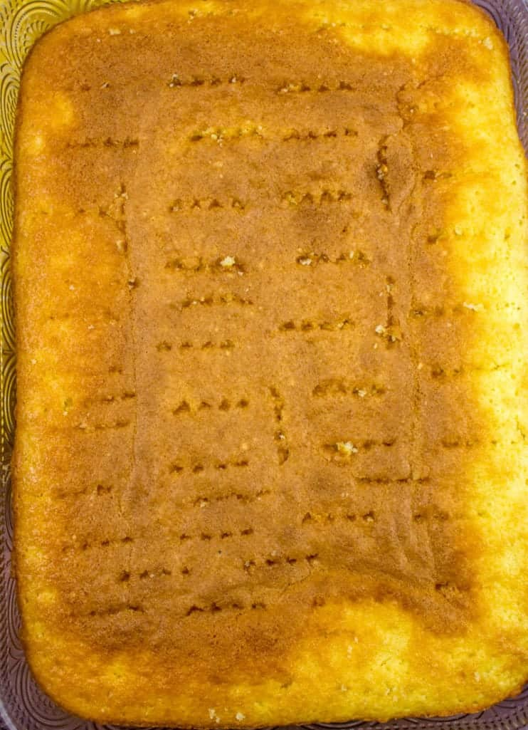 butter cake mix baked in a 9x13 baking dish with holes poked in it