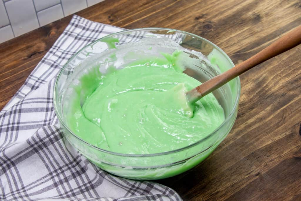 green food coloring stirred into cake batter in a glass bowl