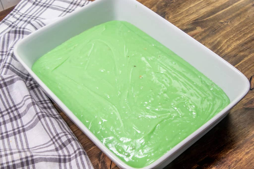 green pistachio cake batter poured into prepared baking dish