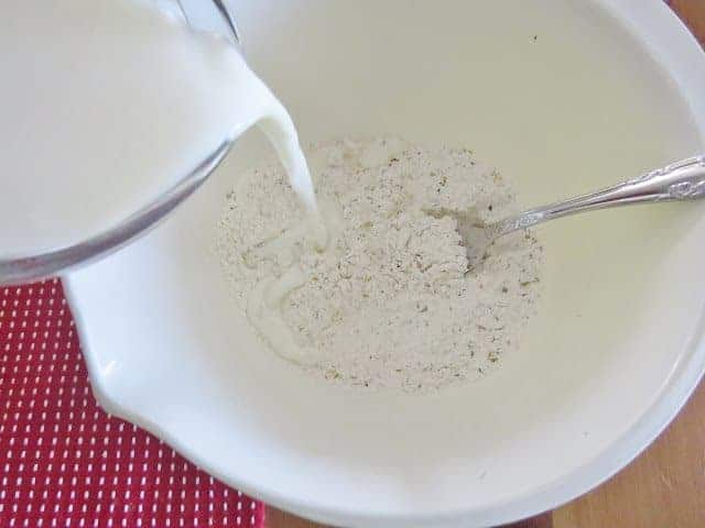 milk being poured into flour mixture in a white bowl