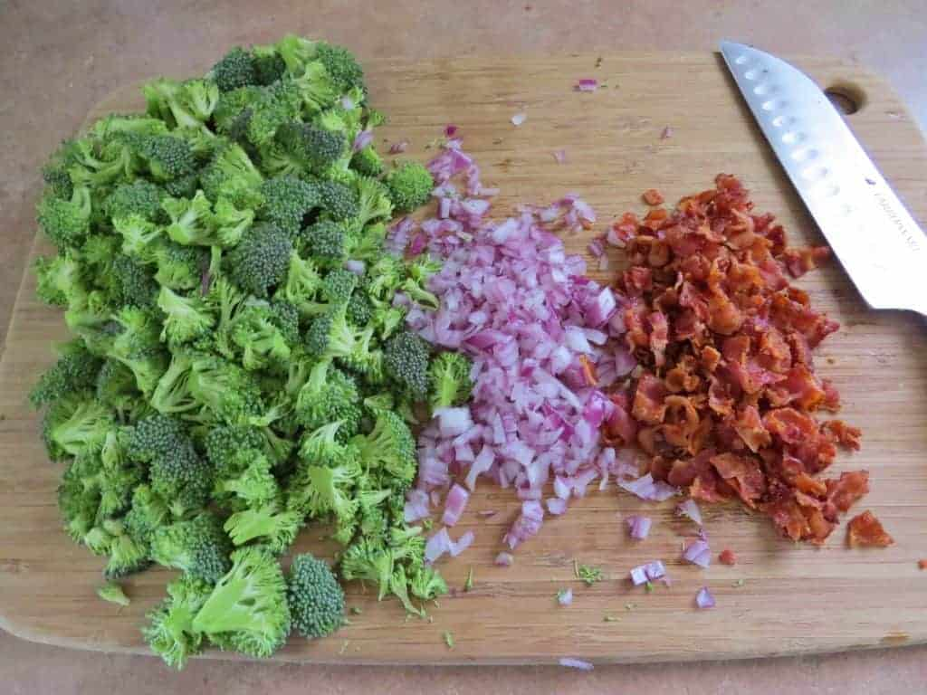 chopped broccoli, diced red onion, crumbled and cooked bacon on a wooden chopping board with knife