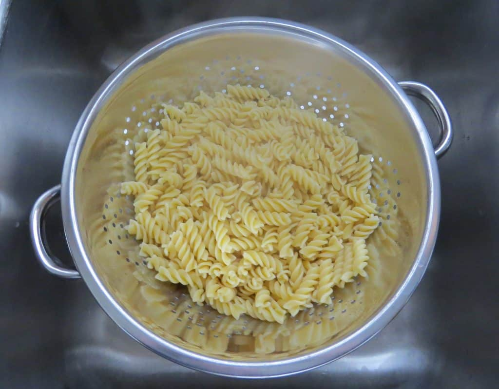 draining excess water from rotini pasta in a metal strainer