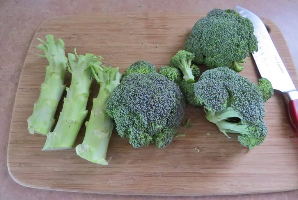 how to chop broccoli, remove florets from the stem, displayed on a wooden cutting board with a chef's knife