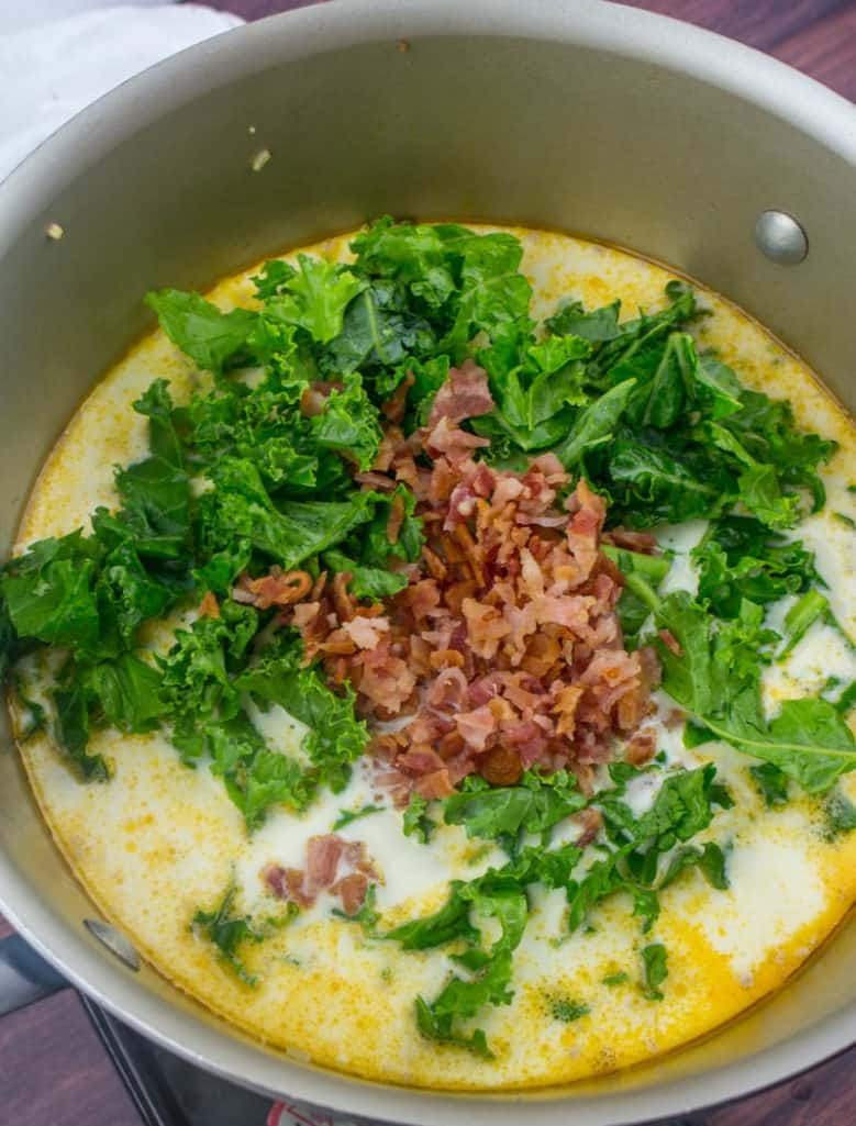 chopped kale and chopped bacon added into stock pot