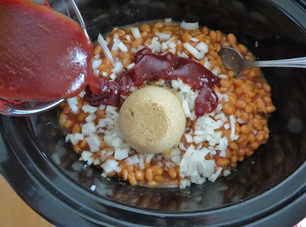 barbecue sauce added to brown sugar, diced onions, pork and beans in a crock pot