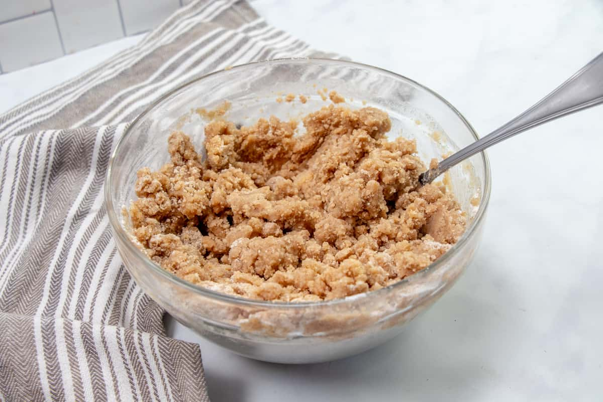 melted butter combined with flour, cinnamon and brown sugar mixed with a fork in a bowl