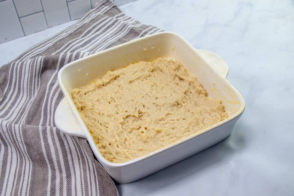 crumb cake batter spread into an white square baking dish