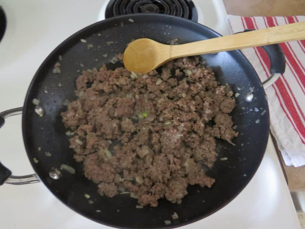 browning ground beef in a nonstick skillet with diced onion and a wooden spoon