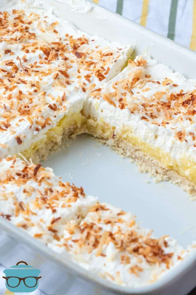 fully finished, Coconut Cream Pie Bars shown in the pan with two slices cut out and topped with toasted coconut