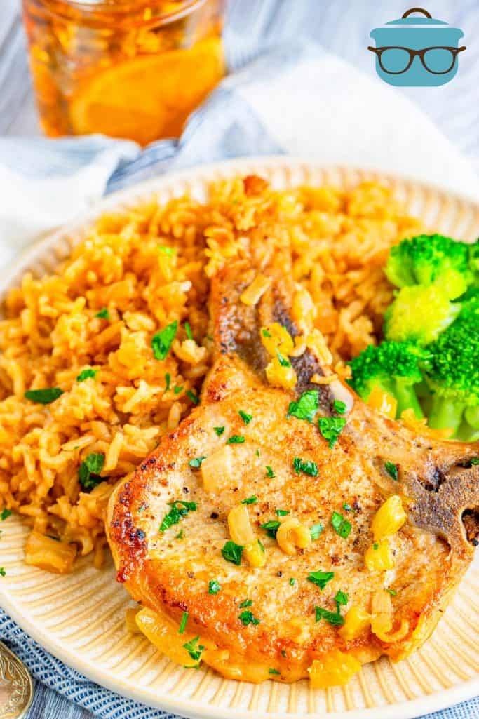 Baked Pork Chops and rice shown served on a white plate with a serving of broccoli