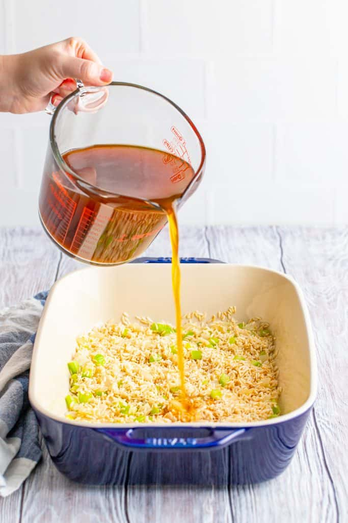pouring beef broth over rice ad celery and onion mixture in a rectangular baking dish