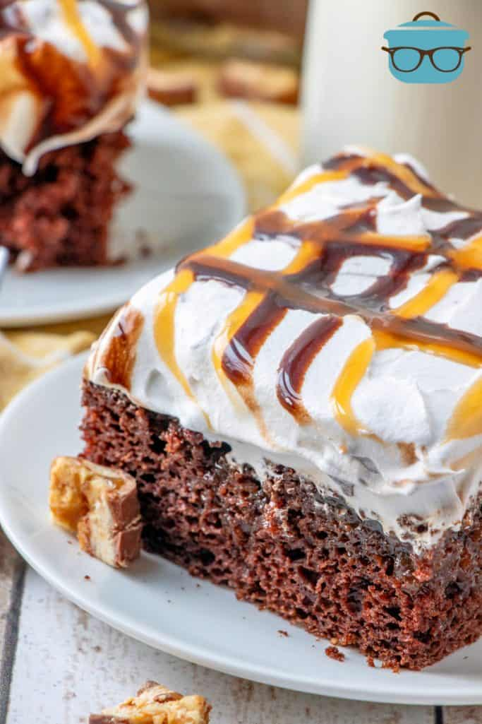 slice of Snickers Poke Cake on a small white plate with pieces of chopped Snickers candy bars scattered around